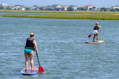 A pair of women paddleboard along the inlet in Murrells Inlet, SC on Tuesday, September 10, 2013. Copyright 2013 Jason Barnette