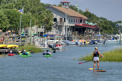A woman paddleboards along the inlet behind a group of kayakers in Murrells Inlet, SC on Tuesday, September 10, 2013. Copyright 2013 Jason Barnette
