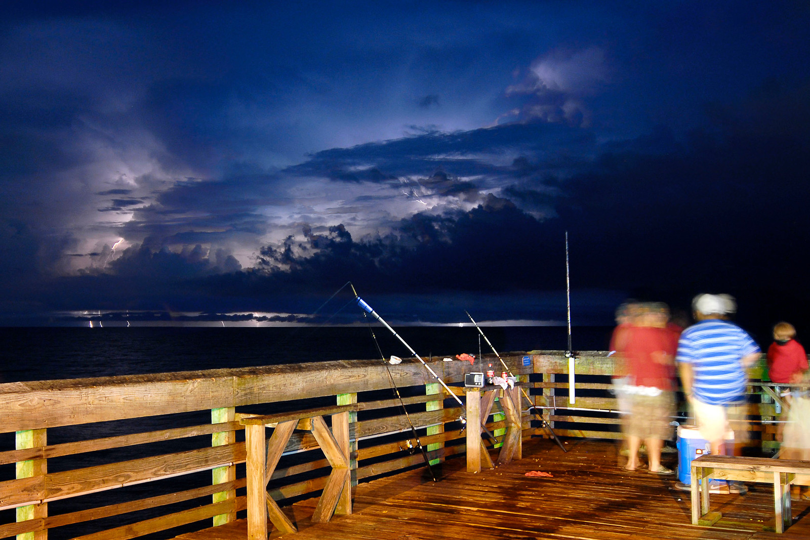 People enjoy fishing on Pier 14 as well as the view of a thunderstorm as several bolts of lightning flash across the horizon at sea in Myrtle Beach, SC on Wednesday, July 11, 2012. Copyright 2012 Jason Barnette