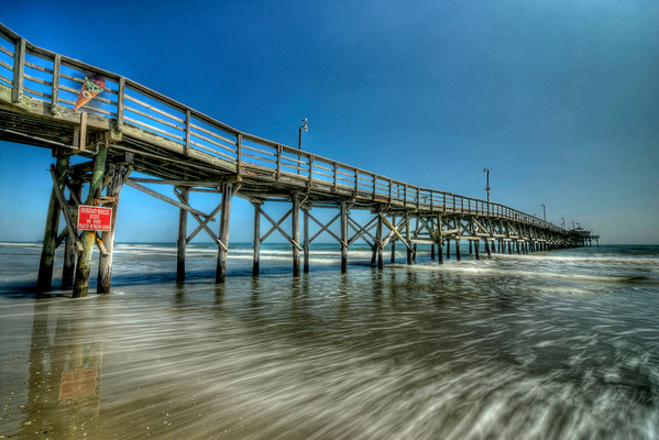 Waves rush under the Cherry Grove Pier in Cherry Grove Beach, SC on Wednesday, March 14, 2012. Copyright 2012 Jason Barnette