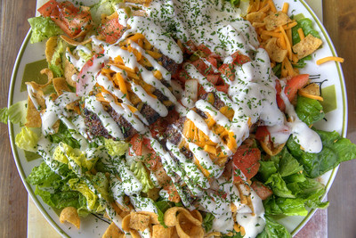 The delicious Poorman Taco Salad, spread out on an enormous plate and loaded with lettuce, tomato, onion, Frito chips, cheese, two large hamburger patties, and ranch dressing, at Mikki's Schoolhouse Diner in Port Royal, SC on Saturday, February 21, 2015. Copyright 2015 Jason Barnette  Mikki's Schoolhouse Diner is a locally owned restaurant located inside an old one-room schoolhouse. The schoolhouse was moved to it's current location in a small shopping village in Port Royal from nearby Yemassee. The restaurant is owned and operated by Mikki and Jeff Rolaine, along with Jeff's daughter Arastatia, making it a truly family operated business.