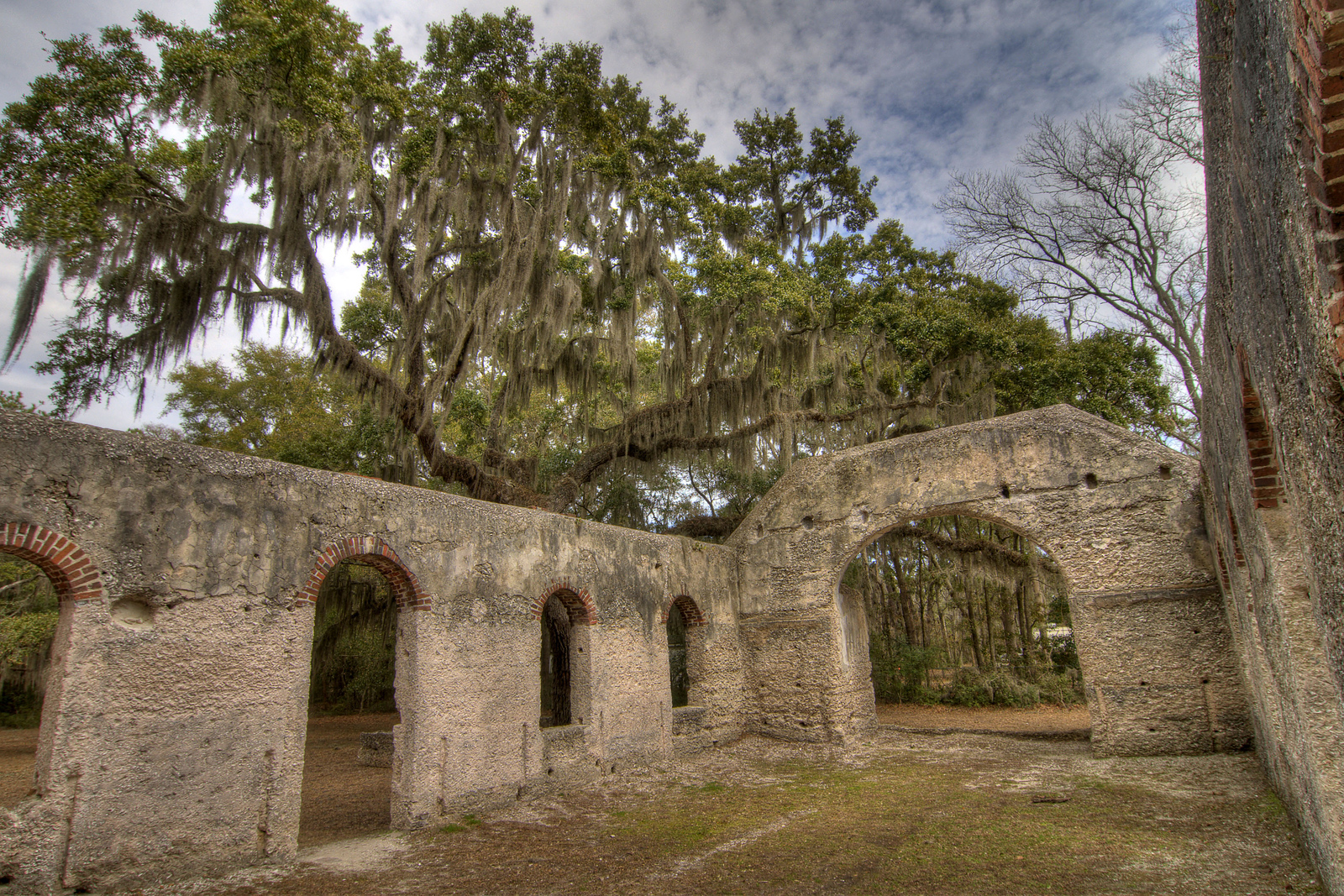 View through the absent roof at the Chapel of Ease Ruins in Saint Helena Island, SC on Sunday, February 22, 2015. Copyright 2015 Jason Barnette The chapel was building in the mid-1700's to serve the families of plantation owners on Saint Helena Island. In 1886 a forest fire destroyed the church, leaving only the walls and a single pillar standing. Today the grounds are maintained by Parish Church of St. Helena. The ruins are open to the public 24/7 for respectful exploration, and permits can be acquired for photo shoots and weddings.