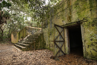 An open door inviting visitors at Fort Fremont Historical Park in Saint Helena Island, SC on Saturday, February 21, 2015. Copyright 2015 Jason Barnette  Fort Fremont consists of several concrete artillery batteries built 1898 in response to the Spanish-American War. The fort was intended to defend local Naval Station Port Royal from invading ships during the war. The fort was deactivated in 1921. Over the next eight decades the property switched hands between several private owners until 2004 when the Trust for Public Land and Beaufort County Council bought the property.   Today the property is open to the public to explore the ruins of the concrete batteries. The area is only lightly maintained, and visitors enter at their own risk. However, it is a rare and thrilling place to explore.