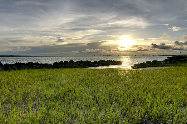 The sun lingers over a bank of clouds across Charleston Harbor from Sullivan's Island, SC on Sunday, July 6, 2014. Copyright 2014 Jason Barnette