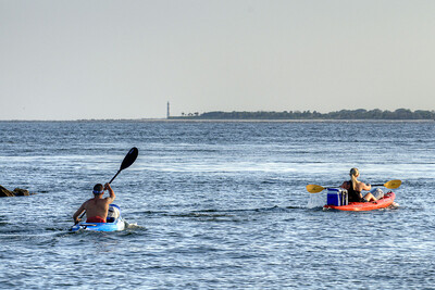 A couple kayak across the water, with the Morris Island Lighthouse in the distance, near Sullivan's Island, SC on Saturday, September 7, 2013. Copyright 2013 Jason Barnette