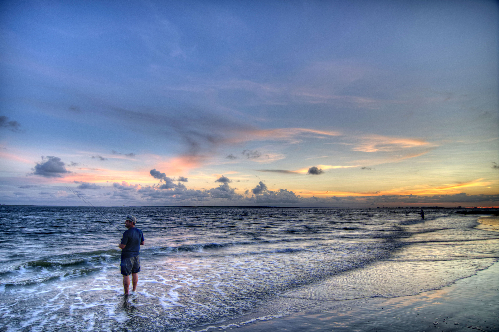 A man fishes in the ocean during sunset at Sullivans Island, SC on Friday, July 19, 2013. Copyright 2013 Jason Barnette