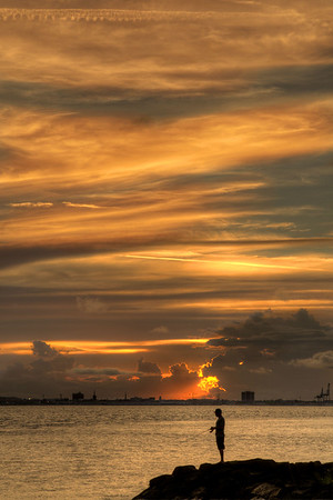 A man fishes at sunset on Sullivan's Island, SC on Sunday, July 6, 2014. Copyright 2014 Jason Barnette