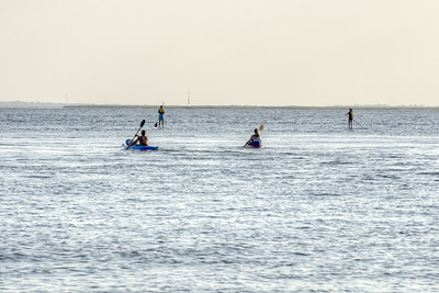 A couple kayak behind another couple paddleboarding across the water near Sullivan's Island, SC on Saturday, September 7, 2013. Copyright 2013 Jason Barnette