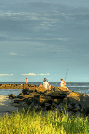 People enjoy fishing and sightseeing just before sunset at a public beach access on Sullivan's Island, SC on Sunday, July 6, 2014. Copyright 2014 Jason Barnette