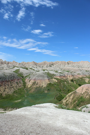 Various colors of sedimentary rock form layers across the landscape. Pinks, yellows, tans, and green grass outline the area of the Badlands in South Dakota.