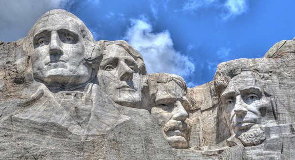 Mount Rushmore National Memorial features 60 foot carved faces of four of the United States Presidents - George Washington, Thomas Jefferson, Theodore Roosevelt and Abraham Lincoln.