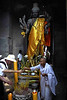 Prayers at the entrance of Angkor Vat before a huge statue of Vishnu, Cambodia