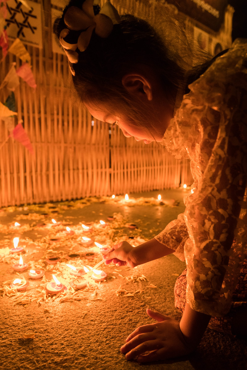 Lighting Candles for the Yi Peng festival in Chiang Mai