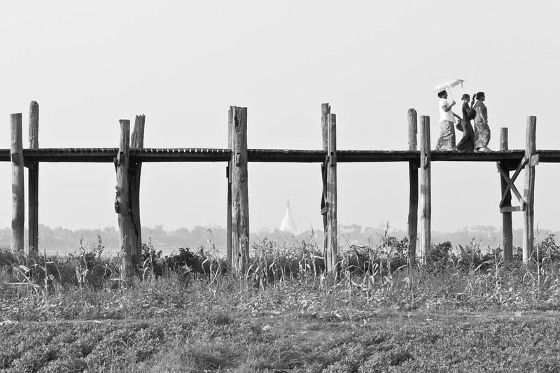 Three women cross U Bein's Bridgein the late afternoon, Amarapura