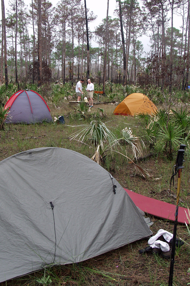 The first nignt of the hike was spent at 10-mile camp. In the background, Robert Kirby and Bruce Davidson treat water from a nearby Cypress Dome. <br /> PHOTO CREDIT: Donn Brown / Florida Trail Association