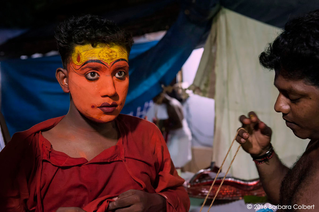 A Theyyam performer dresses for the pre-dawn ritual.