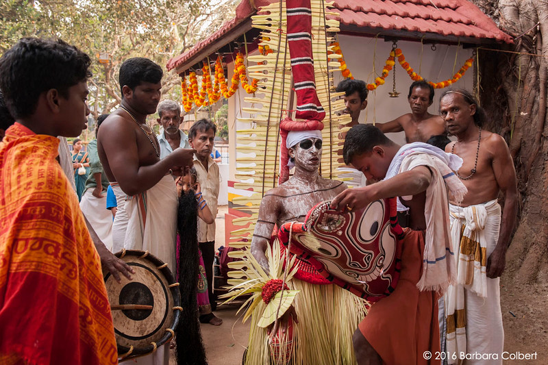 The Theyyakaran is dressed in a towering straw headdress and painted mask.