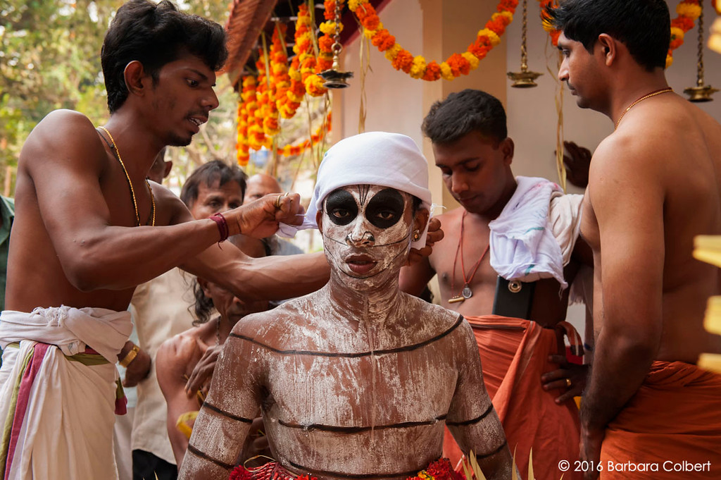 After his wild dance around the temple courtyard, assistants help the Theyyakaran prepare for the next stage of the ritual.
