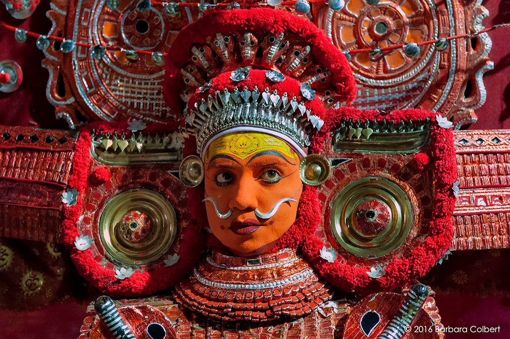 Wearing an elaborate headdress, the performer's transformation to the female deity, Bhagavati, is complete.