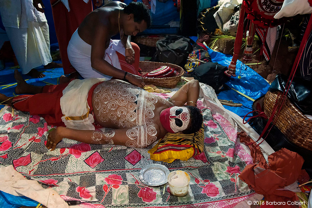 Body and face paint is applied to another performer who will become Kuttichathan.