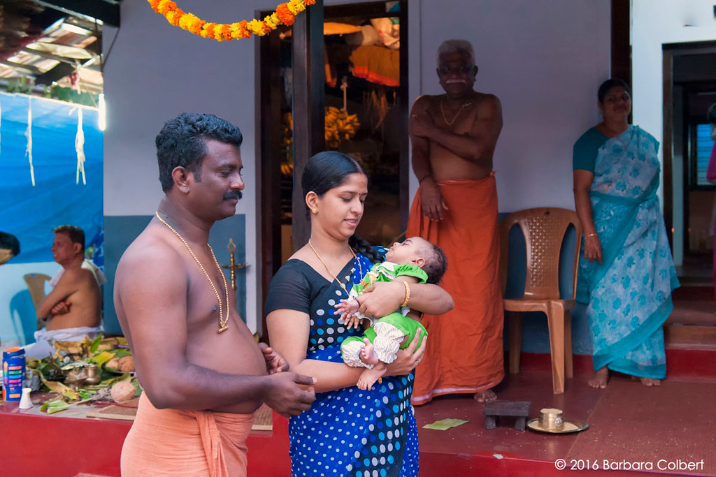 Parents seek the Theyyakaran's blessing for their infant.