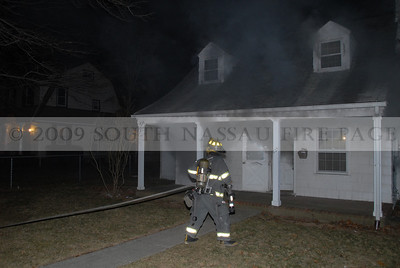 Member of Engine 731 stretches the first 1 3/4 attack line to the rear of the dwelling.