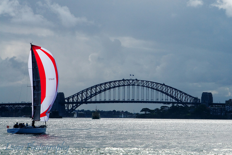 Sailboat passing the Sydney Harbour Bridge