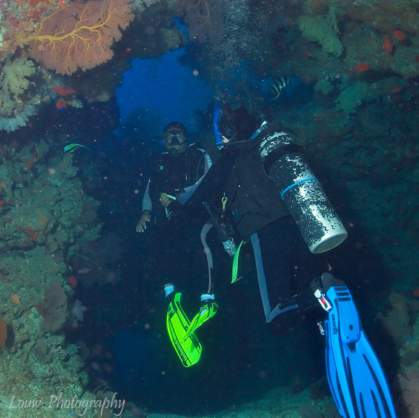 Scuba divers entering a cave at the Great White Wall, Rainbow Reef, Taveuni, Fiji