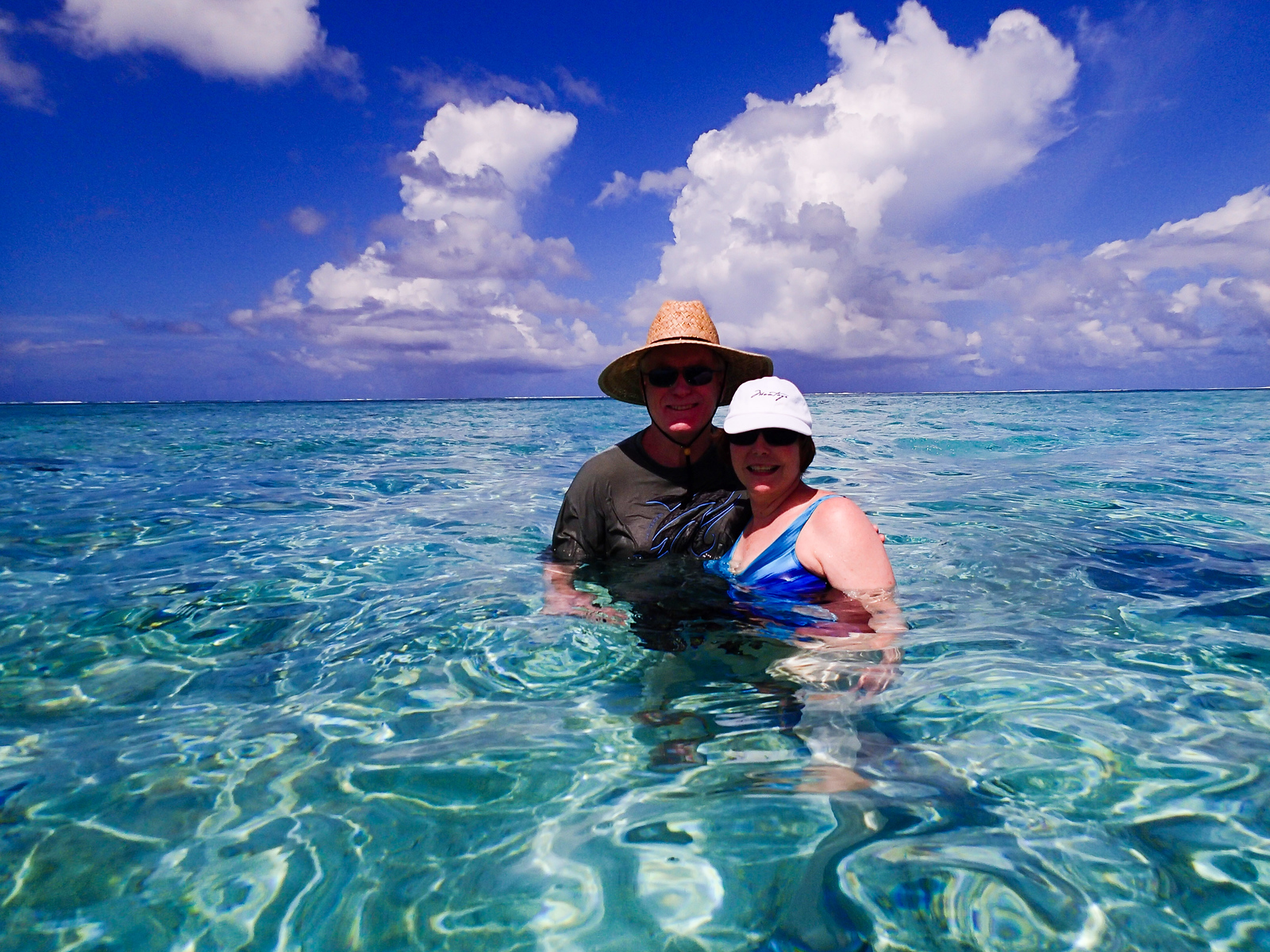 On a luxury cruise to Bora Bora, a man and woman stand in turquoise water surrounded by a blue sky and white clouds.