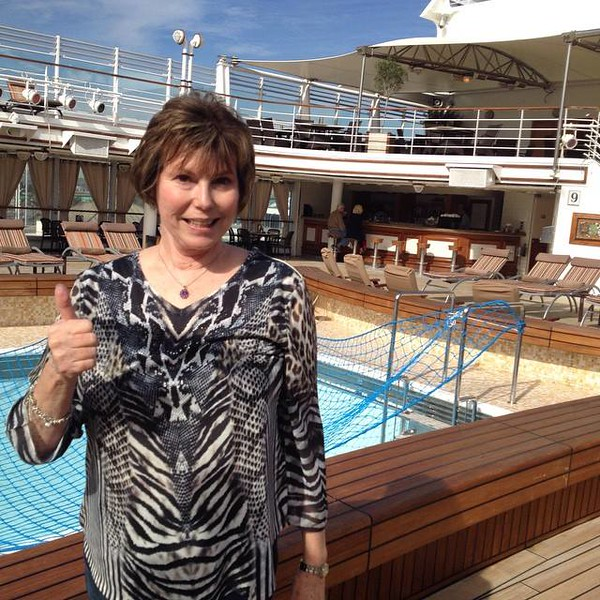 A woman gives a thumbs up by the pool at the beginning of a luxury cruise.