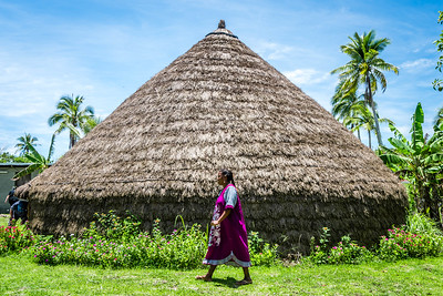 Kanak woman walking by chief's hut