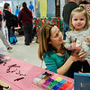 Hannah Bray, 2, held by Emily Butler, strings beads onto pipe cleaner during South Street Elementary School's annual science fair in Fitchburg on Saturday, April 8, 2017. SENTINEL & ENTERPRISE / Ashley Green