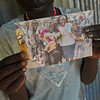 South Sudan. Girl showing a picture of her family. The girl is separated from her parents due to conflict and war. She now lives at a childrens home in Juba.