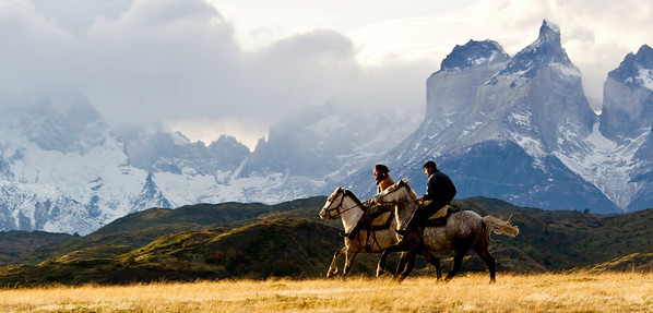 Two gaucho's riding across the flat lands in front of the horns, Torres del Paine, Chile