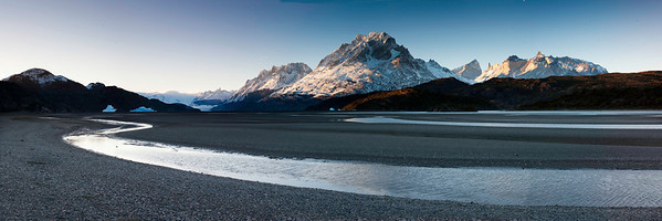 The beach at lago grey with icebergs on the left and mountains in the background