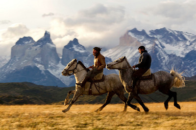 Two gauchos ride in front of the horns at sunset in Torres del Paine