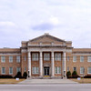 Allendale County Courthouse<br /> <br /> The Allendale County Courthouse, constructed in 1921-1922, is significant as the county's first and only courthouse. Allendale County, the last county established in South Carolina, emerged in 1919 from parts of Barnwell and Hampton counties, jurisdictions thought at the time to be too large to govern effectively. Plans for a courthouse actually began with the legislative act establishing Allendale County; therefore, this courthouse is not merely the only extant building in the county tied closely to the county's founding but clearly the most significant public building in the county. It is also important as an example of the public design work in South Carolina of G. Lloyd Preacher, noted Augusta and Atlanta architect and native son of Allendale County. The A.J. Krebs and Company, general contractors of Atlanta, was engaged to carry out the building's construction. The courthouse is a two-story yellow brick and limestone-accented building whose central block with pedestaled pediment is dominated by a monumental, unengaged, flat-roofed Neoclassical Revival portico. The portico features four massive limestone columns and responding pilasters of the Tuscan order, a classical entablature, and a brick and limestone parapet. Immediately to the rear [northeast] and connected to the historic courthouse by a narrow two-story hyphen is a large office and courtroom building that was completed and occupied in 2004. The new building's construction was part of a larger project that included the overall reconstruction of the historic courthouse's interior and rehabilitation of its exterior, following a devastating arson fire that destroyed much the building's interior on the morning of May 18, 1998. The interior's restoration, in plan and detail, is based upon the 1921 architectural drawings by G. Lloyd Preacher and Company. Listed in the National Register August 1, 2007.