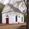 "White Church<br /> <br /> (St. Thomas & St. Dennis Parish Episcopal Church; Brick Church) White Church, or St. Thomas & St. Dennis Parish Episcopal Church, was constructed in 1819 and occupies the site of the older parish church of St. Thomas, which was built about 1706 but which burned in 1815. During the Reconstruction period, the church was the scene of the 1876 ""Cainhoy Massacre,"" a serious riot between whites and blacks which developed when some white men from Charleston journeyed to Cainhoy to attend a Negro Republican meeting. The blacks fired upon the white men with guns they had hidden in a vault at St. Thomas churchyard. The church, charming in its simplicity of design, is a uniquely beautiful example of a small, rural parish church of the early 1800s. The church, with its Classical Revival or late Federal features, is made of stucco over brick with a medium gable roof made of tile. A high-arched doorway with a fanlight capped by a five-panel arch is set between pilasters. The side facades are identical. A balcony above the inside door was added about 1858. In 1937 the church was restored by Henry F. Guggenheim. An unusual and distinctive auxiliary building is the vestry, with hipped roof on one end and chimney on the other, giving the appearance of a half-completed building. A cemetery dating from 1782 is included in the nomination. Listed in the National Register September 22, 1977."