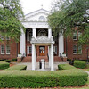 Calhoun County Courthouse<br /> <br /> Calhoun County Courthouse was built in 1913 and designed by renowned South Carolina architect William Augustus Edwards. The courthouse is a two-story brick, Georgian Revival building with a colossal Doric portico on the south elevation. The tetrastyle portico projects from a central three-bay entrance pavilion. The columns of the portico are of stuccoed brick with the proportion and detail of the Greek Doric order: no bases, the diameter broad in relation to the height, and annulets on the lower part of each capital echinus. The entablatures of the portico are executed in wood. It consists of a bipartite architrave, followed by a Doric frieze, with alternating triglyphs and metopes. A taenia beneath the triglyphs features wooden guttae. The courthouse has a hipped roof. A cupola at the crest of the roof is octagonal, painted white, with open arcaded sides, an entablature, and an octagonal dome of pointed profile, sheathed in metal and crowned with a windvane. The cross-axis plan courthouse was built to serve the newly formed Calhoun County, named for South Carolina Statesman John C. Calhoun. The county seat of St. Matthews donated $20,000 toward construction costs for the courthouse and two prominent local residents donated the construction site. Interior details are restricted to the courtroom, where they are used to reinforce the authority of the judge, as representative of Law, Order, Justice, and Calhoun County. Listed in the National Register October 30, 1981.