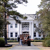 Black River Plantation House<br /> <br /> (Rice Hope Plantation, Black River; International Paper Company House) Black River Plantation House is a significant example of Neo-Classical Revival style of architecture in Georgetown County. Built in 1919 by James A. Waddell, it stands on a high bluff at the apex of a hairpin turn in the Black River north of Georgetown and commands a superb view of the river and old rice fields along its banks. The land upon which the house stands has historically been known as Rice Hope Plantation, Black River. In front of the house on the riverbanks is Post Foot Landing at which Waddell built a cement dock with brick steps leading up the bank to the front lawn of the house. The house is two and one-half story house clad in weatherboard, with a hipped roof with a ridge and four external brick chimneys. The riverside façade is considered the front elevation. The portico is supported by four massive wooden columns with Corinthian capitals. A semi-circular fanlight appears in the pediment. The roof of each of the sun porches is surrounded by a wooden baluster and rail. The interior is appointed with finely detailed architectural components manufactured by the Miller Manufacturing Company of Richmond, VA. The house served as a single family dwelling until it was purchased by the International Paper Company in 1942, after which it was used by company employees and guests as a resort. Listed in the National Register March 2, 1994.