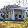 """C. Granville Wyche House<br /> <br /> The C. Granville Wyche House, built in 1931, is primarily significant as an excellent example of depression-era Italian Renaissance architecture. It also has importance because of the distinguished legal career of its owner, C. Granville Wyche, who lived in the house from 1931 to 1988. Designed by Atlanta architect Silas D. Trowbridge, the ornate façade is Italian Renaissance with some Beaux Arts influences. As a """"country estate"""" for a successful attorney with a large family, the Wyche house was one of the most expensive and elaborate residences constructed in Greenville during the 1930s. The symmetrical form, low-pitched tile roof, wide eaves with brackets, full-length, first floor windows and recessed door are all typical of the primary Italian Renaissance style. Beaux Arts influences may be seen in the massive portico, balustrades, grouped classical columns and pilasters, window crowns, and keystones. While the two Neo-Classical Revival styles were no longer fashionable in much of the country, they combined to create a high-style residence for a leading Greenville attorney. Plans for an elaborate formal garden, leading from the left wing, were originally drawn by the architect but were never carried out by the Wyches. A small grotto, original to the landscape design, with deep pool and edged by large boulders and cement mortar inscribed with the names of the Wyche children, is placed at the rear of the formal garden space, contributes to the property. An unpainted barn dating from the mid-1930s also contributes to the property. Listed in the National Register September 2, 1993."""