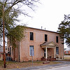 Hampton County Jail<br /> <br /> The Hampton County Jail, constructed 1879-1880, is significant as a public facility designed and used to enforce the law as well as the racial segregation policies of the American South in its administration of local justice for the ensuing century following Reconstruction. The jail was the only holding facility for newly- arrested persons in Hampton County until it closed in 1976. It is also significant architecturally as a unique surviving example of a small, late nineteenth century county penal facility with an architecture reflecting various alterations during its one hundred-plus year history. The jail is two stories in height and three bays wide by two bays deep, with a central, one-story entry portico on the facade and a service porch at the rear. The jailkeeper's living quarters occupied the first floor, while the second floor was dedicated to the cellblocks for both white and black prisoners, including both men and women. The jail was dramatically altered in 1920, circa 1925, and a third time in the 1960s, with the first renovation adding a rear extension to the first floor for additional living space for the jailer, the second renovation modifying the jail cells on the second floor, and the third renovation dividing the first floor rooms on the northeast side into additional jail cells. The building nevertheless retains many of its original features, including a six-celled iron cage system that occupies the northeast side of the second story, but it also reflects a number of significant architectural alterations that document the building's ongoing modification to meet the changing correctional needs of the community. Listed in the National Register June 23, 2011.
