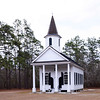 Stoney Creek Independent Presbyterian Church<br /> <br /> Constructed ca. 1833, Stoney Creek Independent Presbyterian Chapel is the only pre-Civil War structure remaining in the village of McPhersonville. This village was built on high ground away from the rice fields in the midst of a tall pine forest. Built by the planters of Prince William Parish who resided in the village during the summer months, the one-story frame building is in the Greek Revival style with later Victorian features. Since it was created as a summer chapel, Stoney Creek is plain and austere, as one would expect for a Presbyterian congregation. It boasts an imposing façade with four Doric columns supporting a pedimented roof, sash windows with semi-elliptical transoms, and a round stained glass window. An octagonal steeple was added in 1890. The lantern of the steeple features arched 6-light windows on four sides. A small wooden finial rests atop the conical roof. The interior is very simple with plain plaster walls, original wooden pews, and wide pine floors. The site was used as a hospital and the grounds for a campsite by Federal troops. Regular worship at the chapel dwindled due to the economy and lack of growth in the community. As a result the congregation was dissolved in 1967. The chapel is maintained by the First Presbyterian Church of Beaufort. Listed in the National Register May 22, 2002.