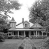 """Broadus Edwards House<br /> <br /> (Paul Garber House) Built in 1905, this one and one-half story weatherboard Queen Anne style residence is set on a brick foundation, with columns, a two-story left turret under a tent roof and a right bay surmounted by a pedimented cross gable. A dormer with twin vertical one-over-one windows pierces the steeply hipped composition roof. The central front door is enframed with rectangularly paned transom and sidelights. Window sash are all one-over-one, typical of the period. Shutters decorate the turret. The house was built by Broadus Edwards, prominent Batesburg merchant, mortician, and town councilman. A neighbor described the Edwards residence as """"the summer social center of the street, with a fine lawn, well kept orchard, and tennis court."""" After Edwards moved to Augusta, Georgia in 1926, the house was purchased by Paul Garber, a prominent merchant in Batesburg. Listed in the National Register July 6, 1982."""