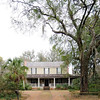 "Scott House<br /> <br /> The Scott House is one of the oldest houses in Kingstree and a fine example of mid-nineteenth century vernacular architecture. It was built ca. 1843 by Joseph Scott, a wealthy planter, trustee of the Kingstree Academy, and politician who was elected to the state legislature in 1836. The house changed hands many times after Scott's death, its owners including many citizens prominent in local history and politics. The house is a two-story frame building, sheathed in weatherboard, with a side-gabled roof. The façade is three bays wide and features a ""Carolina"" or ""rain porch"" supported by slim, tapered piers. The entranceway on the first floor contains double doors with sidelights and transom. The house rests on a brick foundation, has two exterior brick chimneys, and an embossed tin roof. The windows are six-over-six double-hung sash with full paneled shutters. Listed in the National Register June 28, 1982."