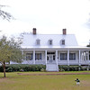 Erwin House<br /> <br /> (Erwinton Plantation & Hunting Club) Erwinton is a one and one-half story, white clapboard structure built upon a raised brick basement. It was constructed ca. 1828 by Dr. William Robinson Erwin. The front façade is characterized by three dormers and a piazza that extends its entire length as well as halfway down each of the side facades. Fourteen square wooden columns extend along the piazza, and similar pilasters ornament the corners of the house and frame the doorways. Erwinton is an example of Bahamian-influenced raised cottage style of architecture. This style was prevalent in the Southeast, particularly on the coast, during the nineteenth century. The dormers were added during the 1950s. Dr. William Erwin, the original owner of Erwinton, his wife and sister-in-law were all excommunicated from Kirkland Church in 1833 for their affiliation with other denominations. They then formed the second Christian congregation, the Disciples of Christ, in South Carolina. They held weekly meetings at Erwinton until 1835 when the present meeting house was completed and dedicated as Antioch Christian Church. Listed in the National Register May 24, 1976.