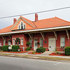 South Carolina Western Railway Station<br /> <br /> Seaboard Air Line Railroad Station) The South Carolina Western Railway Station is significant for its association with several railway companies that played major roles in Darlington's economy in the first half of the twentieth century. The station was completed in 1911. Rectangular in plan, the brick building has projecting rectangular bays at the center of its north and south sides. The hipped roof features a bell-cast profile, red clay tile, and wide bracketed eaves. On the north and south slopes of the roof are intersecting gables, each containing a Palladian window and wood shingle siding. Piercing the roof at the ridgeline are two brick interior chimneys, which are paneled. Windows are double-hung, one-over-one, with sandstone sills and lintels. Doors of the asymmetrical north and south elevations are paneled and have operable transoms. The South Carolina Western Railway was chartered in Darlington on August 26, 1910. The rail line from McBee to Darlington was open to service on May 15, 1911, and the passenger station was completed shortly thereafter. Lawrence Reese, a black master carpenter who had constructed many houses in Darlington, built the station. Listed in the National Register February 10, 1988.