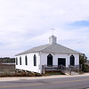 """Pawleys Island Historic District (Pawleys Island Chapel)<br /> <br /> The island exemplifies a way of life in its beauty, its setting and its overall landuse. Pawleys is one of the earliest of South Carolina's summer beach settlements and maintains integrity in the natural relationship of marsh, beach and dune. The unusual number of old houses which have been maintained enhances the natural environment to which they are well adapted. The building style is a variation of West Indian architecture which has been adapted to Pawleys climatic conditions. The original houses on Pawleys are not mansions but summer retreats, sturdily built and large enough to accommodate big families. Designed for the greatest degree of ventilation, with porches on multiple sides and with high brick foundations providing protection against gale tides, many of the 20th century buildings have adhered to the traditional design that has proven well suited to this environment. Since the plantation families resided at Pawleys from May to November, the houses were equipped with large chimneys and fireplaces. Breezeways attached at the rear of the houses led to the kitchens. Servant's quarters were usually one or two room cabins equipped with fireplaces. A few remained at the time of nomination. Other structures important to Pawleys are the wooden docks with open """"summer houses"""" extending into the salt water creek and the long boardwalks with """"summer houses"""" which cross the dunes and offer easy access to the beach. The district includes the central portion of the island, an unspecified number of properties ranging from ca. 1780 to post World War I, and includes shoreline and marshland since these are an integral part of the district both historically and geographically. Listed in the National Register November 15, 1972."""