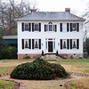 Earle Town House<br /> <br /> The Earle Town House is an architectural, historical, and aesthetic asset. An architecturally distinguished example of a late Georgian dwelling, one of the few extant in upper South Carolina, the residence is one of two houses within Greenville remaining from the city's earliest history. Its park-like grounds, shaded by old trees and enclosed by an ivy-covered grillwork fence, feature the sanded front walk typical of its earlier years, a handsome garden front entrance of grillwork and brick, and an ivy mound approximately 100 years old (built after 1856). A rear garden with fountain is patterned after Edgar Allen Poe's Richmond, Virginia garden. That the home now known as the Earle Town House was built at least by 1810 is indicated by the 1910 birthday celebration marking its 100th anniversary. Outstanding features include distinctive wood and glass detailing surrounding the front door, double front steps, a Palladian window on the second story, hand carved mantels, six paneled doors, and raised paneled dado. The Earle House site was originally part of the plantation of the pioneer Earle family. The family came from Virginia shortly after the Revolution and settled in this wooded, Blue Ridge foothills section. Elias T. Earle, whose father was an early member of the Virginia House of Burgesses, was one of the first members of the family in South Carolina, figuring prominently in the history and development of the Greenville area and of the state. He was a state senator from Greenville District, a U.S. Congressman, a silk grower, a manufacturer, and first Commissioner of Indian Affairs under the U.S. government. Also born in the house was another leading figure, Judge and U.S. Senator Joseph Haynsworth Earle, great grandson of Elias T. Listed in the National Register August 5, 1969.