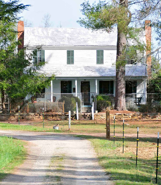 Cureton-Huff House<br /> <br /> The Cureton-Huff House is a two-story frame farmhouse in rural Greenville County which was reportedly built ca. 1820 for John Moon Cureton. Cureton was a prosperous farmer and his house and farm are representative of the rural farmhouses and complexes of the time and region. The house in particular is representative of the vernacular building modes, construction technology, and limited stylistic awareness common to an upper-middle income farmer in a rural community. The house also retains noteworthy Federal stylistic elements in its woodwork. The plan of the house, originally a vernacular hall-and-parlor, was altered prior to the death of Cureton into a central hall plan. Both plans were common to the farmhouses of South Carolina in the antebellum era. The heavy timber-braced frame with its mortise-and-tenon joints, the beaded weatherboarding, and the small-paned window sash were representative features of such houses. The machine-cut L-head brads used in the Cureton-Huff House and the original box locks were common to the houses of the state in the period 1820-1860. Stylistic features of special note include the sunburst motifs and the reeding on the mantels of the hall and the parlor and the chevron ornamentation along the cornices suggest an awareness of the fashionable Neo-classic ornamentation of the Federal period. Outbuildings on the property include a carriage house, a blacksmith shop, several barns and animal pens, two corn cribs, and a garage. Most of the outbuildings date from the early twentieth century. A family cemetery with a low stone wall is also on the property. Listed in the National Register January 13, 1983.